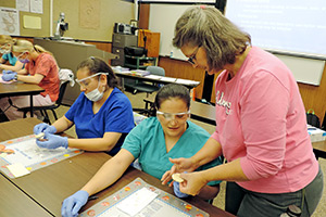 Teacher assisting dental assisting student