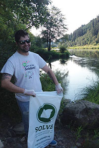 Michael holding a SOLVE Oregon cleanup bag standing in front of the Tyee section of the Umpqua river.